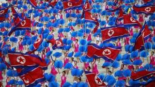 Dancers waving North Korean flags