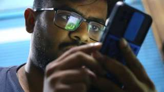 A man tries to use WhatsApp following the outage to services, in Karachi, Pakistan, 4 October 2021