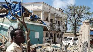 A man stands at the scene of a hotel attack in Somalia