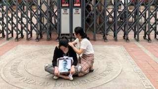 林唯麒的母亲鲁女士抱着孩子的相片坐在学校门前。