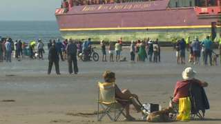 people sat watching barge at Black Rock beach