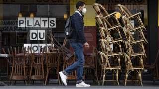 A man walks by an empty cafe in Paris