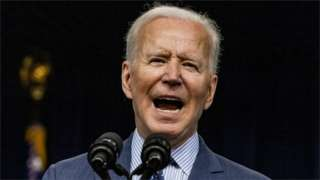 Joe Biden speaking at a microphone with his mouth open
