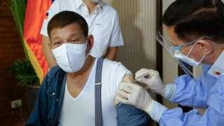 Rodrigo Duterte getting a vaccine shot