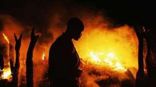 Un combatiente rebelde sudanés del Movimiento de Justicia e Igualdad (JEM) observa la aldea de Chero Kasi en llamas.