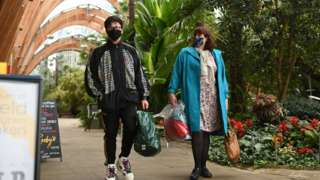 A couple wearing protective face masks, walk through The Winter Garden in Sheffield, in northern England on October 21, 2020