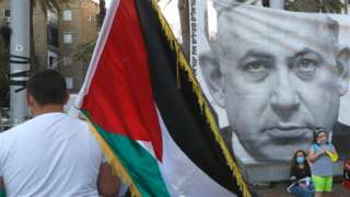 Demonstrator carries a Palestinian flag at a protest in Tel Aviv against Israel's annexation plans (06/06/20)