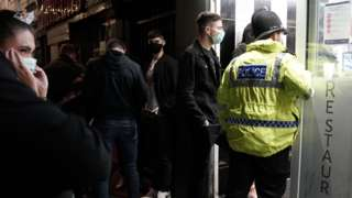 A police officer reminds workers in Newcastle city centre of the 10pm curfew that pubs and restaurants in England are subject to in order to combat the rise in coronavirus cases.
