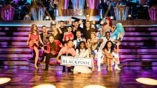 Strictly dancers pose at the ballroom holding a Blackpool sign