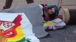 Protestor with arm in concrete barrel