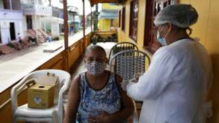 A health worker administers a Sinovac's CoronaVac coronavirus disease (COVID-19) vaccine to Luizete Soares da Silva, 66, outside her house in Anama, Amazonas state Brazil April 1, 2021. Picture taken April 1, 2021.