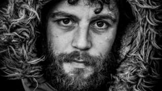 Black and white image of bearded man with fur lined hood up