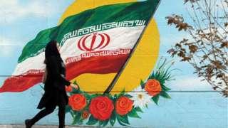 Iranian woman walks past mural in Tehran (file photo)