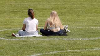 Two Germans sit in a painted circle in a park