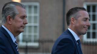 Edwin Poots and Paul Givan pictured in profile from the right hand side, both appear to be in motion