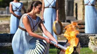 Greek actress Xanthi Georgiou, playing the role of the High Priestess, lights up the torch during the flame lighting ceremony for the Beijing 2022 Winter Olympics at the Ancient Olympia archeological site in Athens, on 18 October 2021