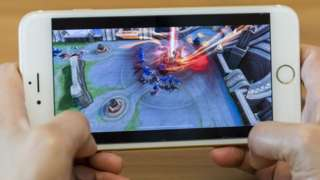 One of Tencent's popular mobile games runs on an iPhone being held by a person