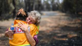 A fruit farmer is comforted by a journalist in Batlow, New South Wales