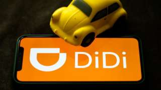 Didi logo on smartphone screen with toy car.