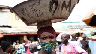 A woman wearing a face mask and carrying a dish on her head in Lagos, Nigeria - May 2020