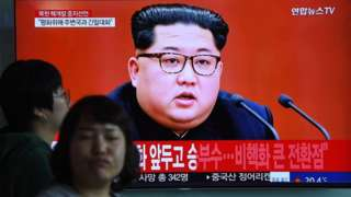 People at a train station in Seoul walk past a television screen showing footage of Kim Jong Un