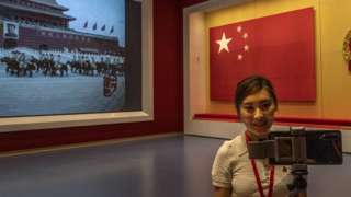 A journalist films next t o a large screen and original national flag at the newly built Museum of the Communist Party of China on June 25, 2021 in Beijing, China.