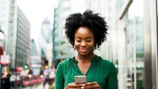 Une femme noire qui regarde son téléphone dans la rue