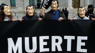 "Protesters outside Spain's parliament in Madrid show part of a banner with the word ""death"". Photo: 17 December 2020"