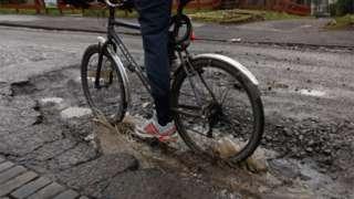 A cyclist rides through a pothole