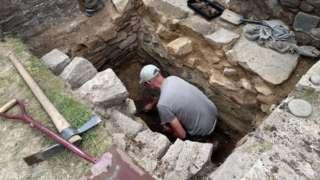 Volunteer excavating the Roman fort wall