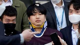 Cho Ju-bin outside the police station, wearing a neck brace