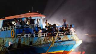 A large fishing ship coming from Libya is about to disembark migrants in Lampedusa, Italy.