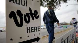 From March: Person walks by polling site in San Antonio, Texas