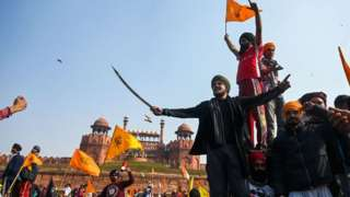 Protesters shout slogans in front of the Red Fort