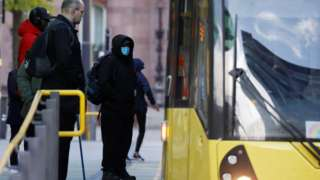 Man in PPE boarding Manchester tram
