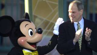 Michael Eisner, CEO and chairman of the Walt Disney Company, gets a pat on the back from Mickey Mouse in 2001