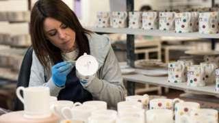Woman painting mugs