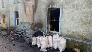 The outside of a burned house where an elderly woman was injured in a house fire and later died