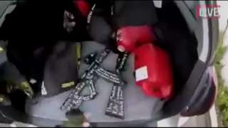 Grab from live stream shows gunman retrieving weapons from boot of car, Christchurch, NZ (15 March)