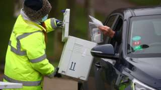 A worker collects a swab from a car window at a test centre in Goldsworth Park, in Surrey