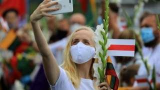 Девушка с телефоном и бело-красным флагом