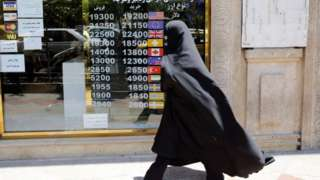 An Iranian woman checks the currency rate as she walks past a currency exchange service in Tehran, Iran, 22 June 2020