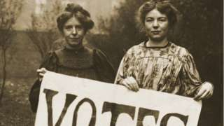 """Annie Kenney and Christabel Pankhurst holding banner proclaiming """"Votes for Women"""""""