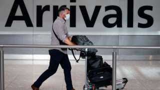 Man wearing a face mask walking through arrivals at Heathrow Airport