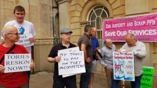 About 20 people gathered outside County Hall to protest against cuts.