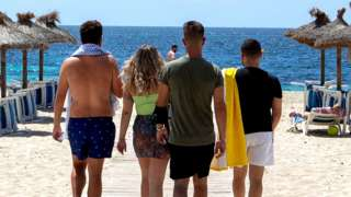 Tourists arrive at Magaluf Beach in Calvia, on the Balearic Island of Mallorca, on 28 June 2021