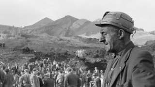Miner with eyes closed wearing pit helmet at Aberfan disaster, as recovery continues behind him