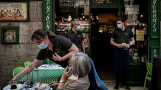 A waiter serves a client at a restaurant in Lyon in June