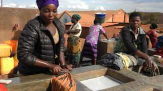 Refugees wash their clothes on June 20, 2018, on World Refugee Day at Dzaleka Refugee Camp in the Dowa district, central region of Malawi