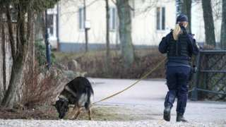 Police officer with a dog patrols at a knife attack site in Vetlanda, Sweden March 3, 2021